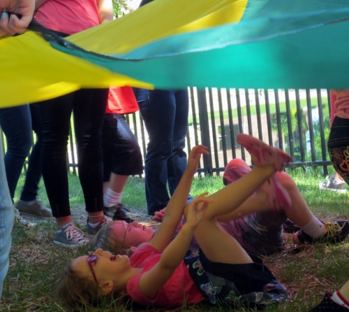 Children play with the parachute during Fun Friday!